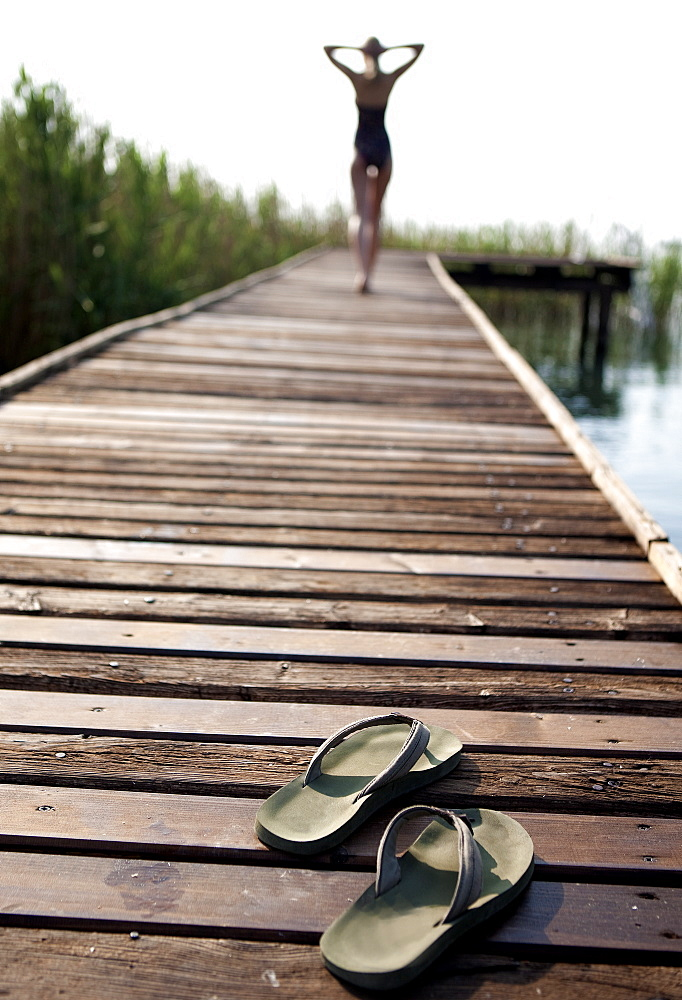 Rear view of woman wearing swimsuit walking along a jetty, hands on head, pair of flip flops in the foreground