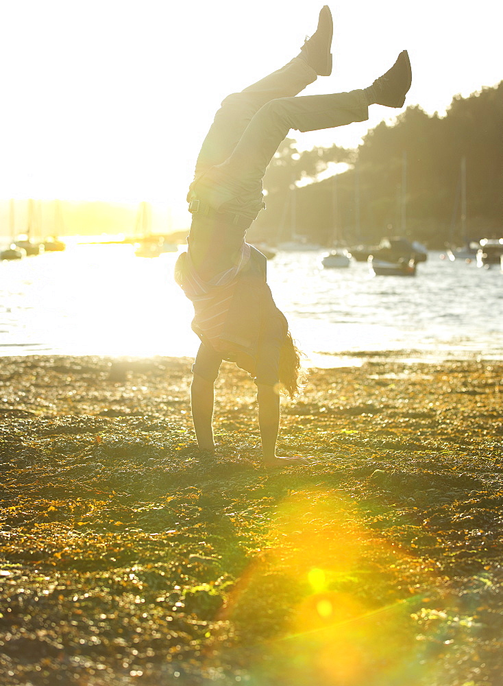 Man doing a handstand on the shore, sea and moored sailing boats in the background, sunlight, Cornwall, United Kingdom