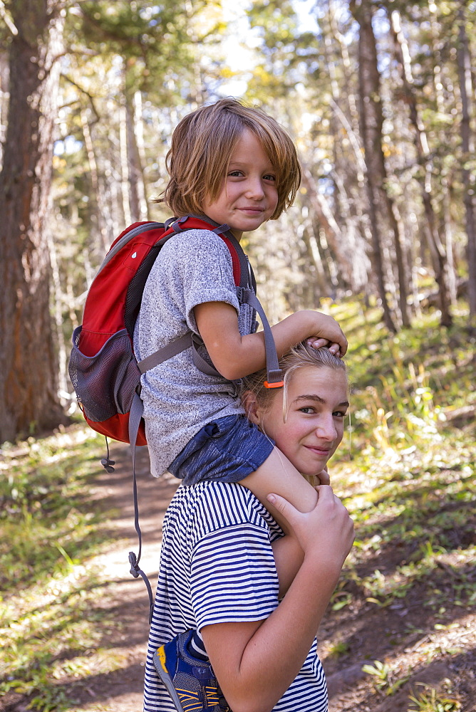 4 year old boy getting ride on sister's shoulders