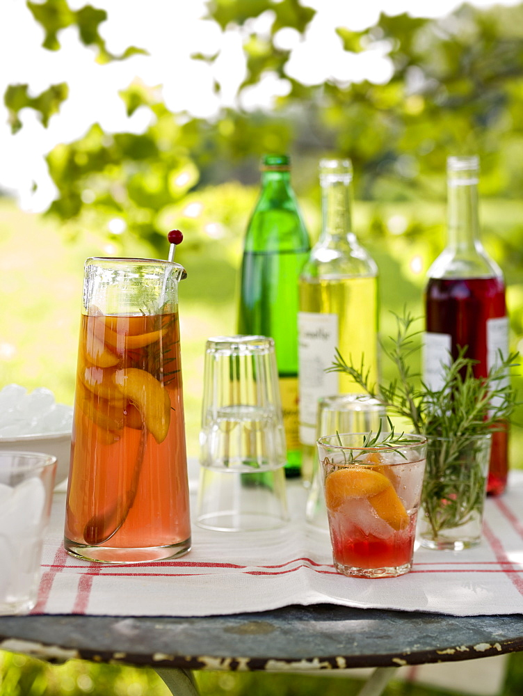 A buffet table set up in a garden for al fresco meal. Drinks, bottles, a jug of punch and glasses, Maryland, USA