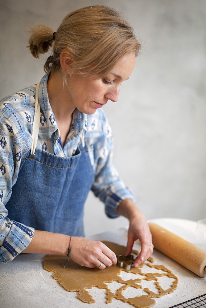 Blond woman wearing blue apron cutting out Christmas cookies - 1174-9261