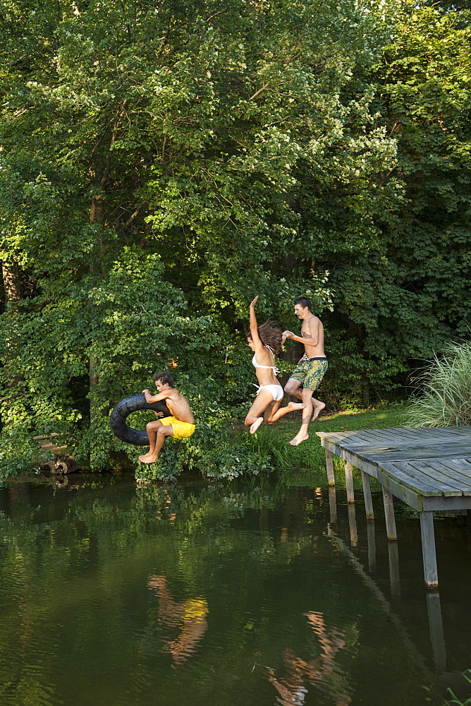 Three young boys jumping from the jetty into a still pool of water, Maryland, USA