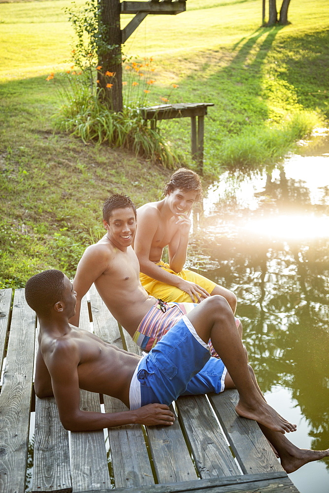 Three boys sitting on a wooden jetty, and sunlight reflecting off the water surface, Maryland, USA