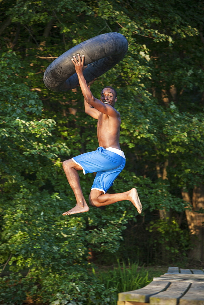 A young person, boy holding a swim float tyre over his head and leaping into the water from the jetty, Maryland, USA