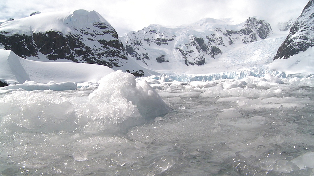 Brash ice in foreground, cascading glacier between snow capped mountains behind. Paradise Bay