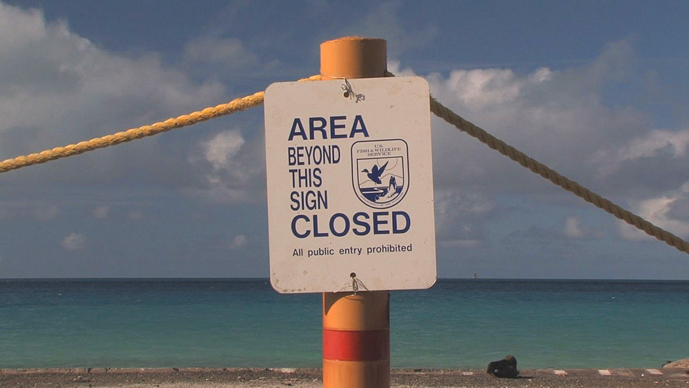Area closed sign. Beach behind (with albatross, turtles and rubbish). Conservation story - rubbish. Midway Island. Pacific - 959-1