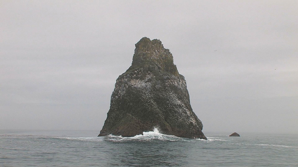 Stack rock at sea, sea bird nesting site - filmed from boat. Northern Pacific, Aleutian Islands. Alaska