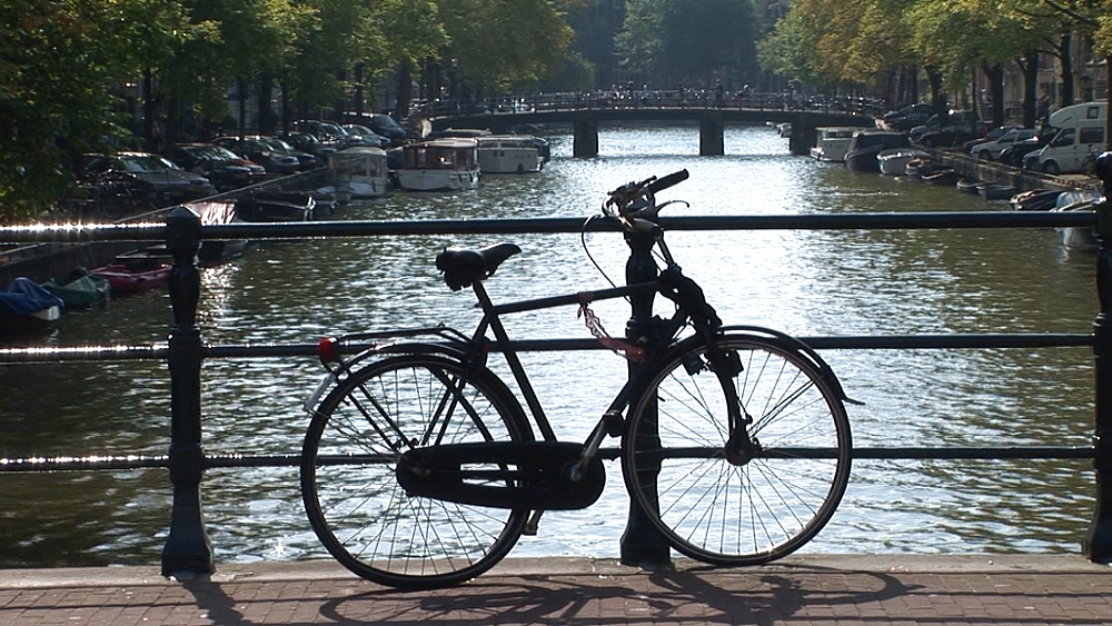Street scene with parked bike by canal. Amsterdam. Netherlands