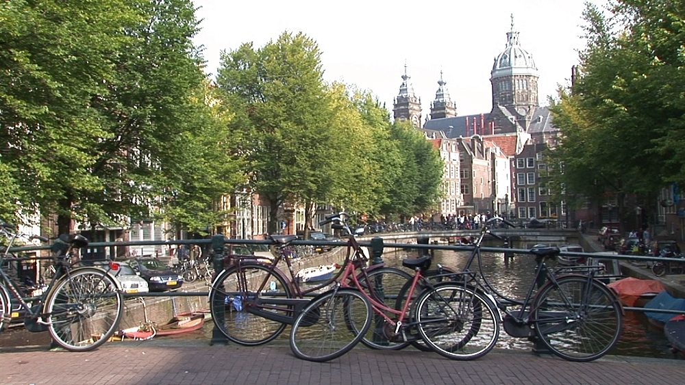 Street scene with parked bikes by canal. Amsterdam. Netherlands