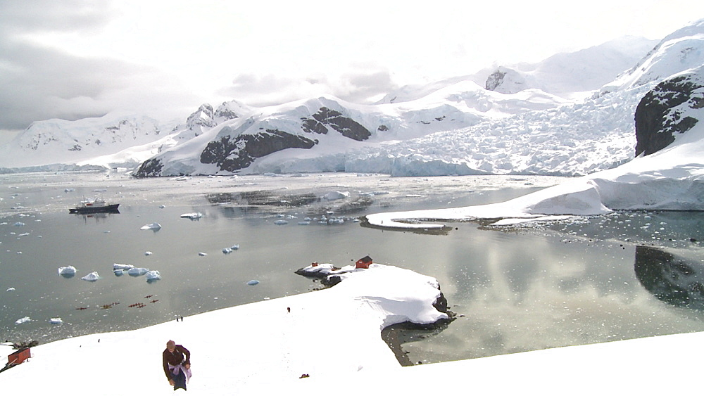 Argentinian Antarctic station from high angle, pull out to wider with hiker. Almirante Brown. Paradise Bay