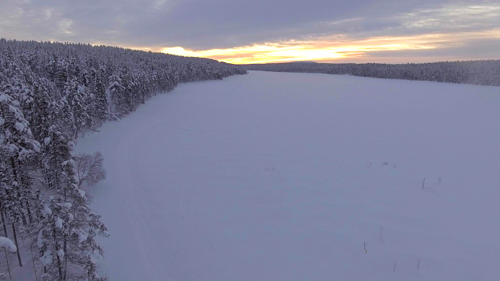 View by drone of Torassieppi Lake (Toras-Sieppi Jarvi) frozen and snow covered in winter at sunset, Finnish Lapland, Finland, Europe