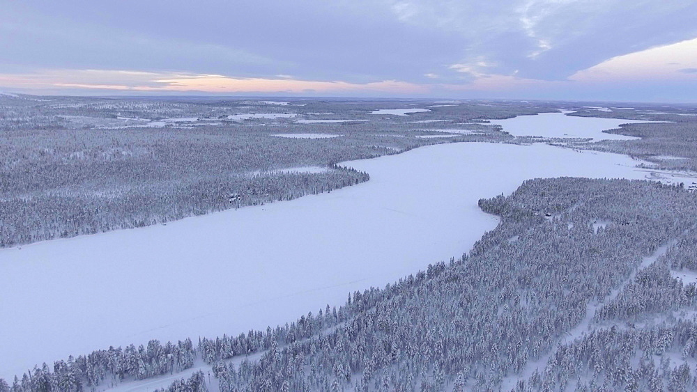 View by drone of winter landscape and snow covered trees near Torassieppi Lake (Toras-Sieppi Jarvi) at sunset, Finnish Lapland, Finland, Europe