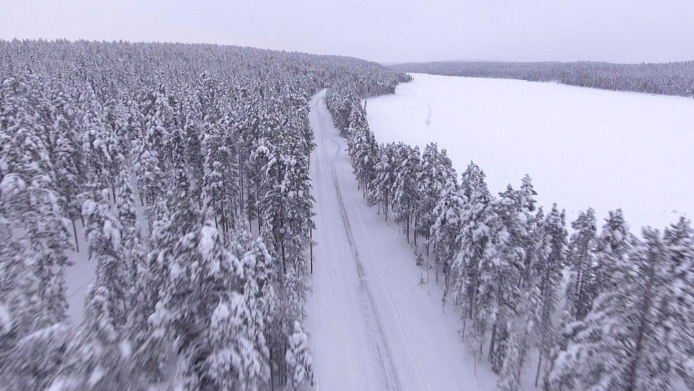 View by drone of snow covered road in winter in Finnish Lapland, Finland, Europe