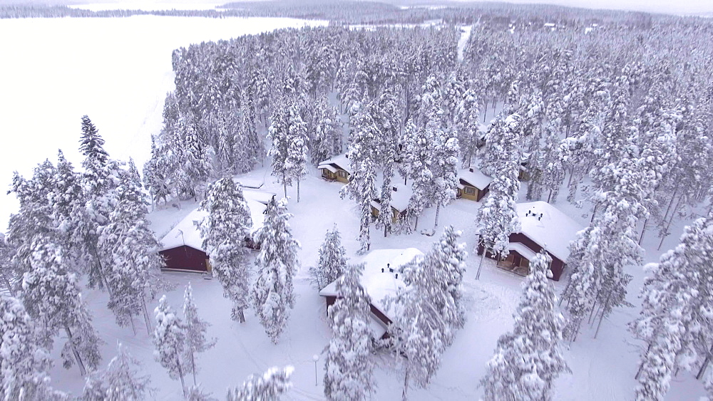 View by drone of Torassieppi Reindeer Farm Cabins covered in snow in winter, Finnish Lapland, Finland, Europe