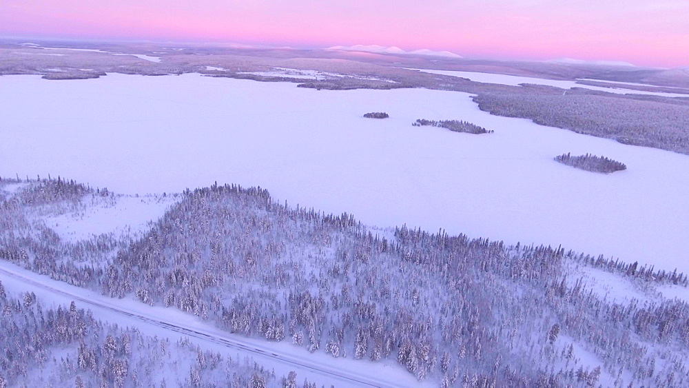 View by drone of snow covered winter landscape at sunset near Akaslompolo, Finnish Lapland, Finland, Europe