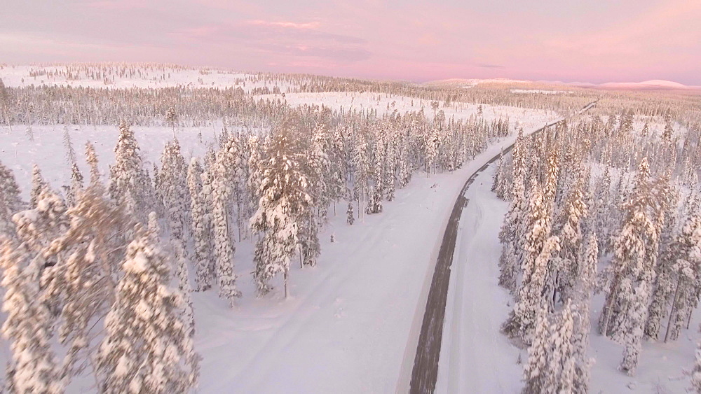 View by drone of snow covered road in winter, near Akaslompolo, Finnish Lapland, Finland, Europe