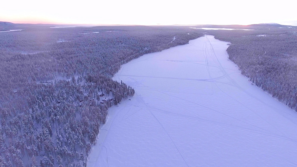 View by drone of snow covered forest and lake in winter landscape at sunset, Torassieppi Lake, Finnish Lapland, Finland, Europe