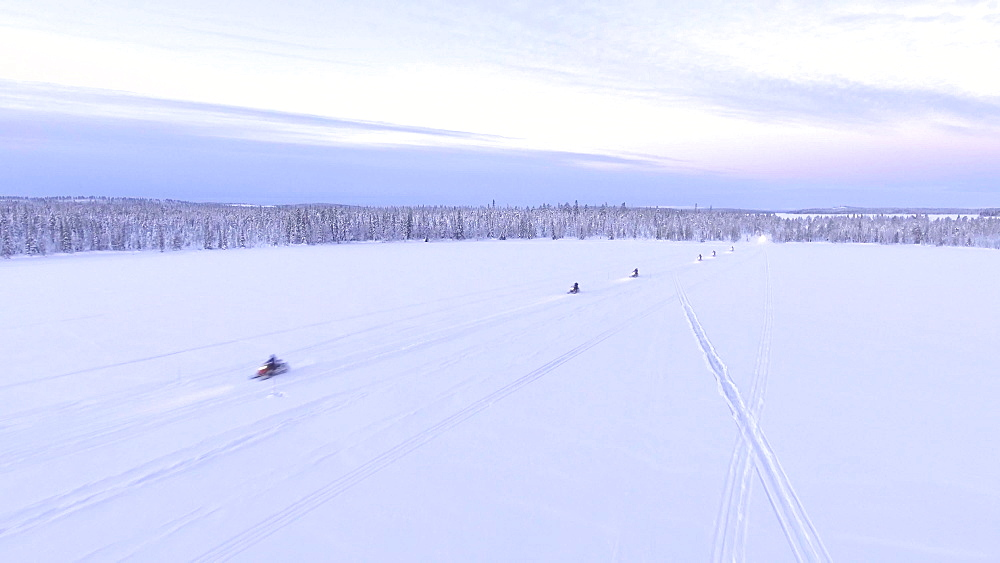 View by drone of snowmobiling on Torassieppi Lake covered in snow in winter, Finnish Lapland, Finland, Europe
