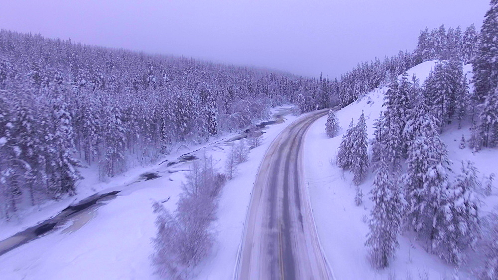 View by drone of driving on a snow covered road in winter, near Akaslompolo, Finnish Lapland, Finland, Europe