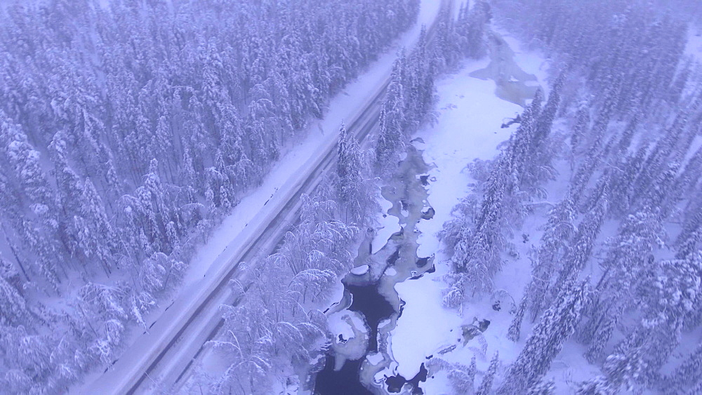 View by drone of snow covered road and frozen river in winter, near Akaslompolo, Finnish Lapland, Finland, Europe