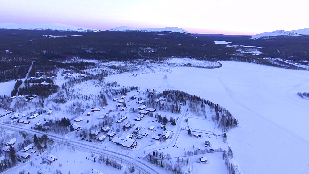 View by drone of snow covered Akaslompolo town and lake in winter, Finnish Lapland, Finland, Europe