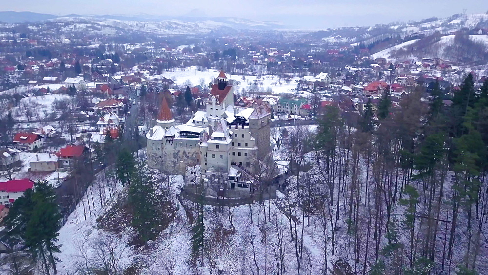 View by drone of Bran Castle covered in snow in winter, Transylvania, Romania, Europe