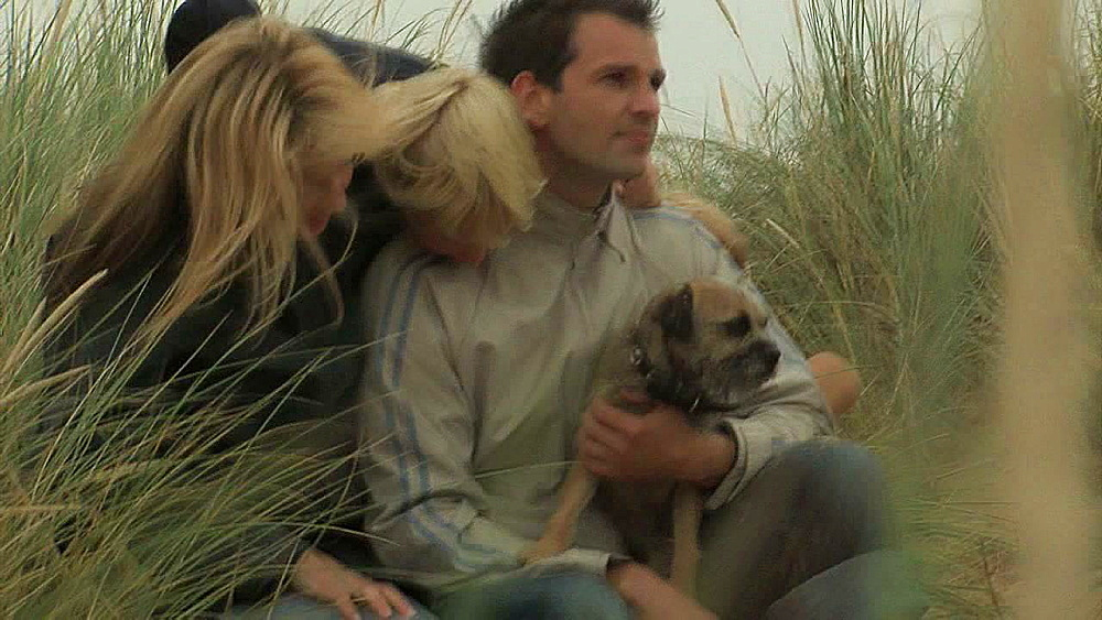 Two Adults and four children cuddling their dog on a sandbank - 1114-1447