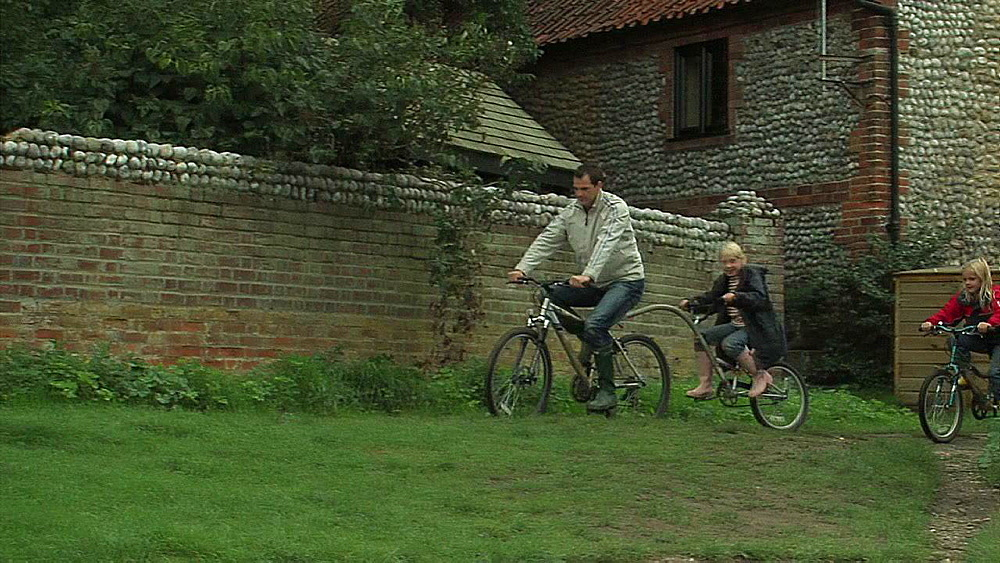 Family going for a cycle around a village