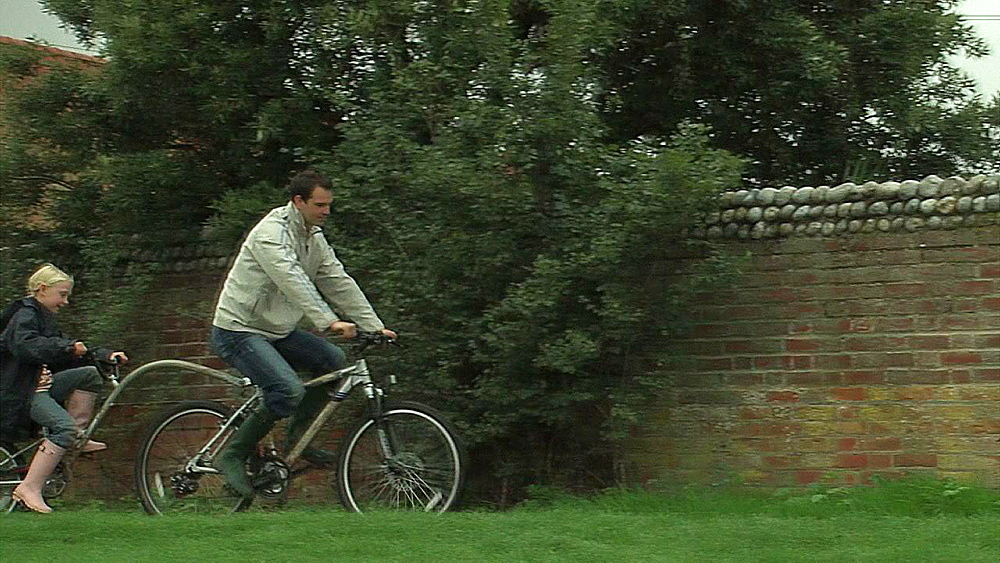 Man and two girls cycling in the countryside