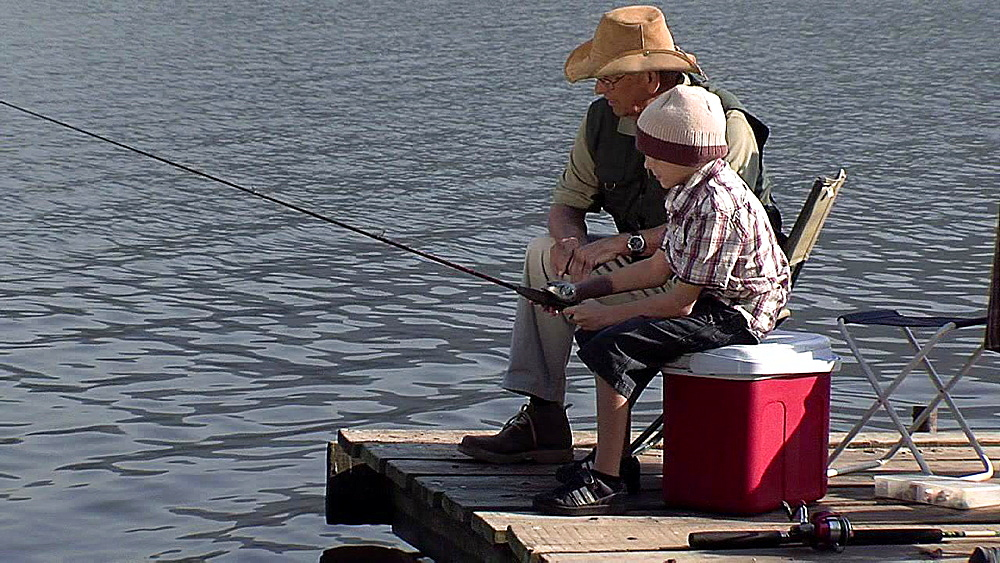 Man with a hat teaching a boy how to catch fish