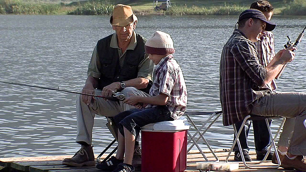 Children being shown how to fish by men