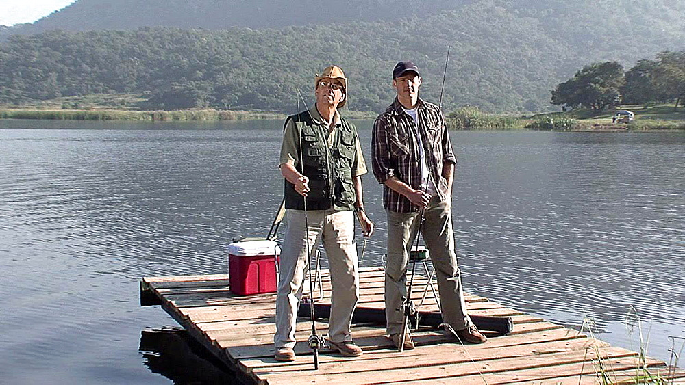Two men holding fishing rods and looking straight ahead