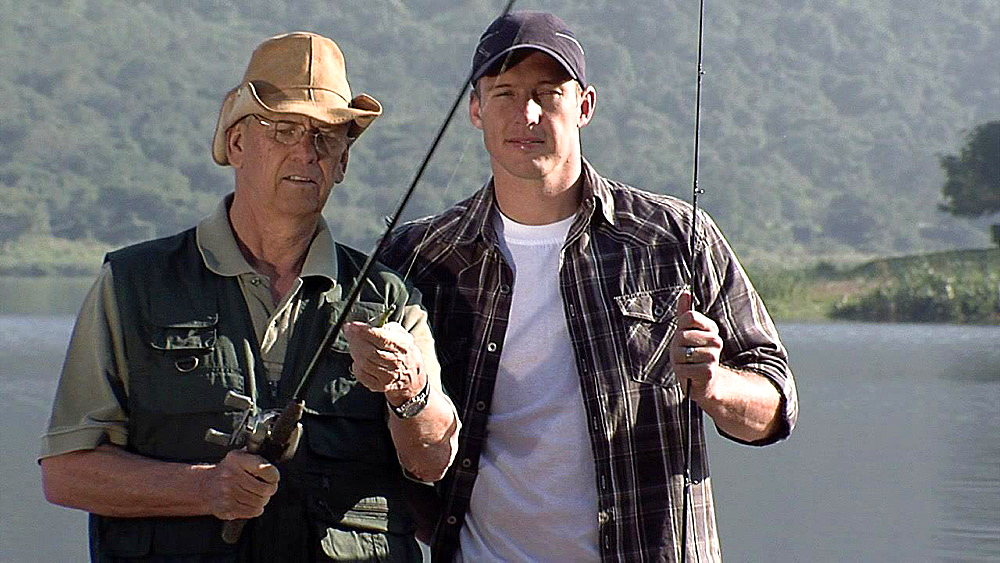 Older man wearing glasses and a younger man wearing a cap standing together holding fishing rods