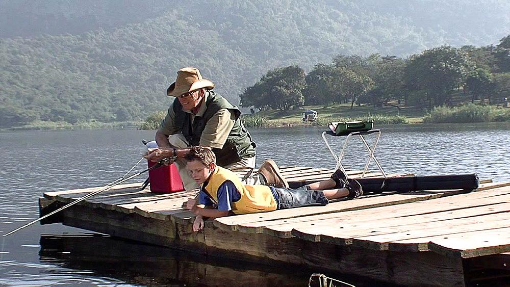Boy lying on a jetty watching water