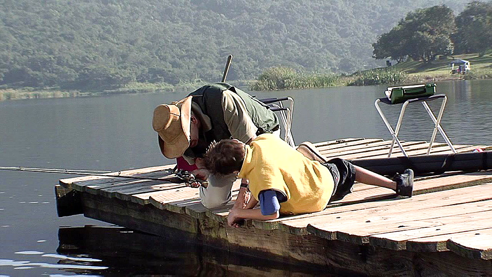 Older man leaning over the edge of a jetty with a boy looking in the water
