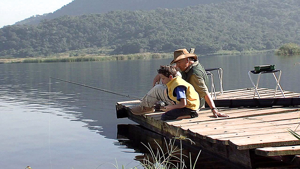 Boy leaning over the edge of a jetty with a fishing rod