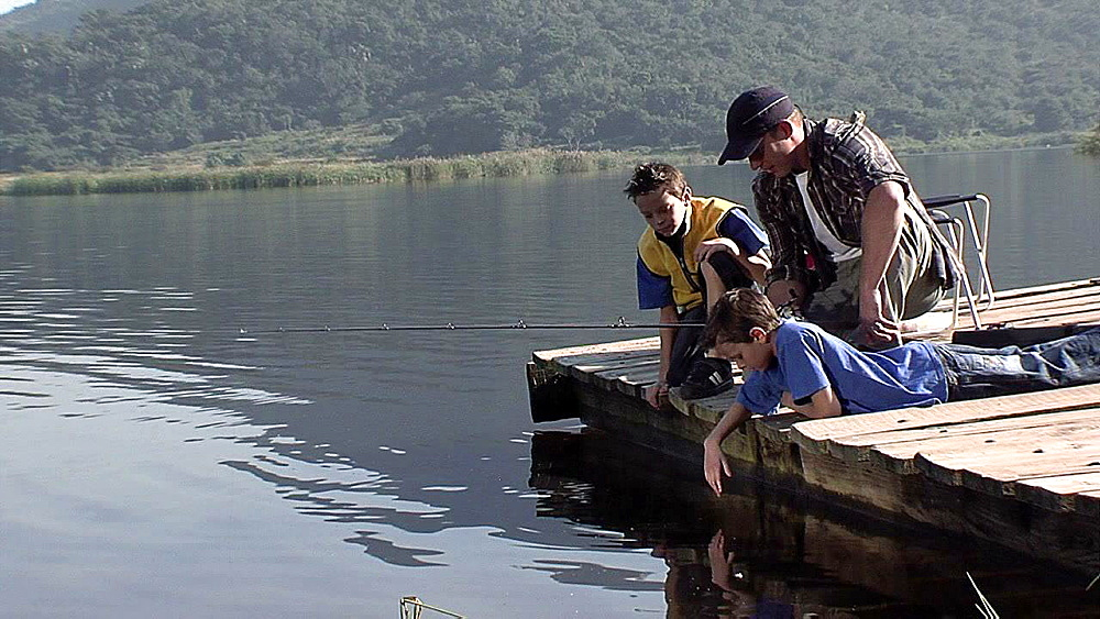 Man and two boys fishing