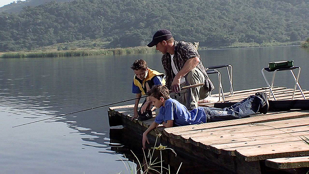 Man and two boys sitting on a jetty
