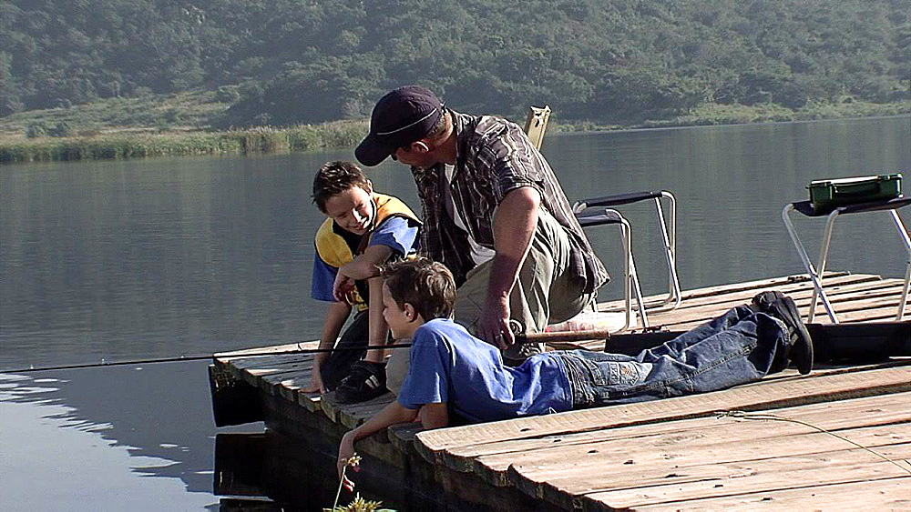 Man and two children sitting on a jetty chatting