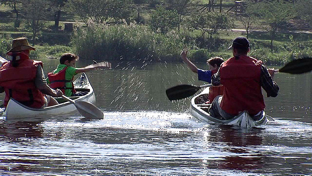 Men and boy canoeing on a lake