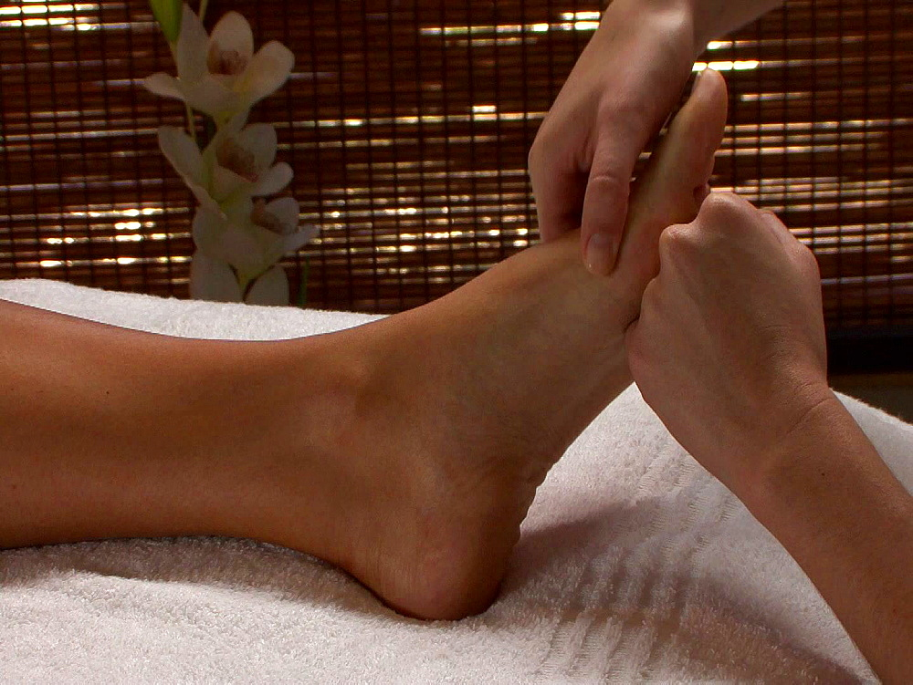 Person lying on a white towel having her foot massaged