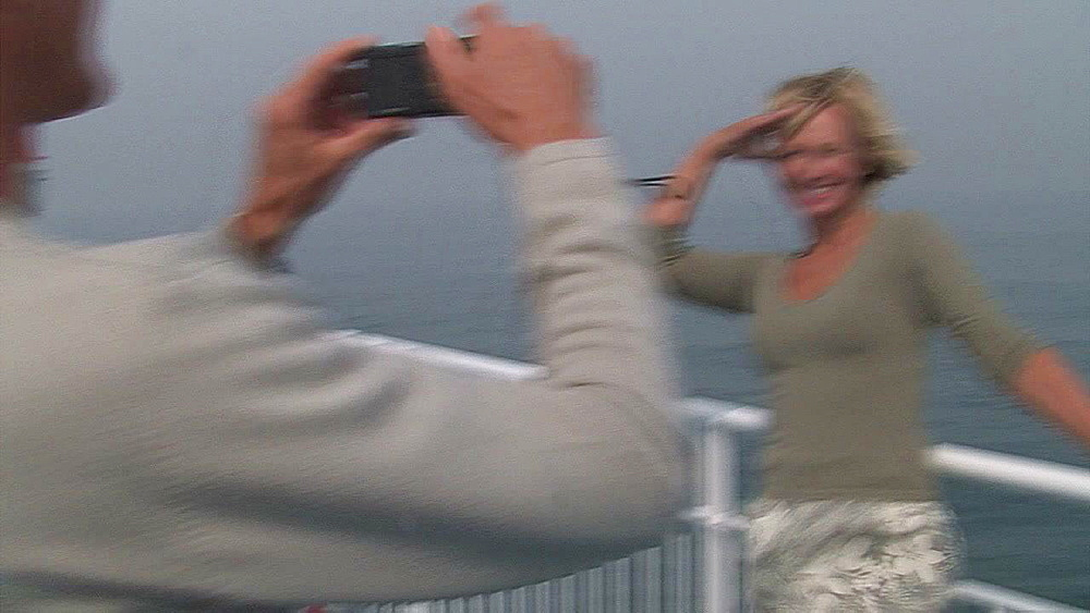 Man takes a photo of his loved one on the deck of his ship