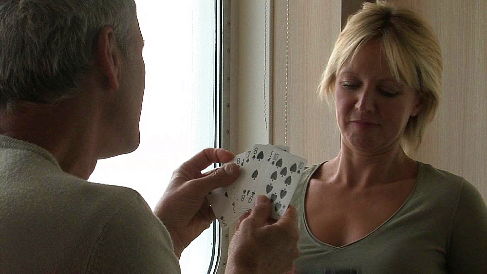 Man holding a hand of cards opposite a blond haired woman