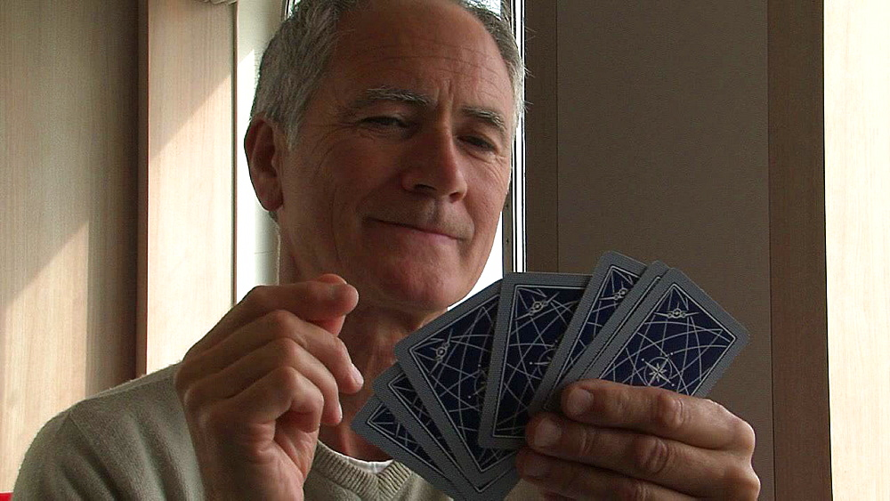 Grey haired man losing at a card game