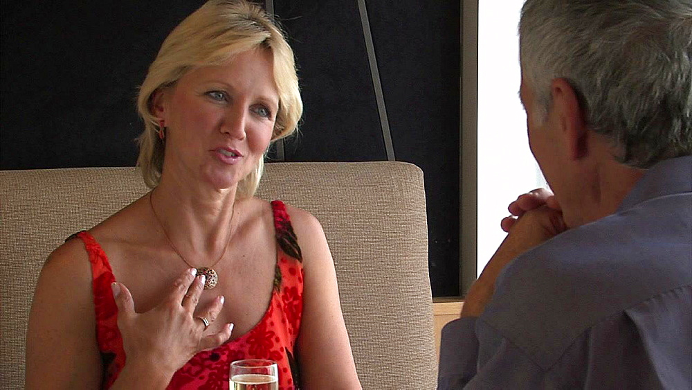 Blond haired woman talking to a grey haired man