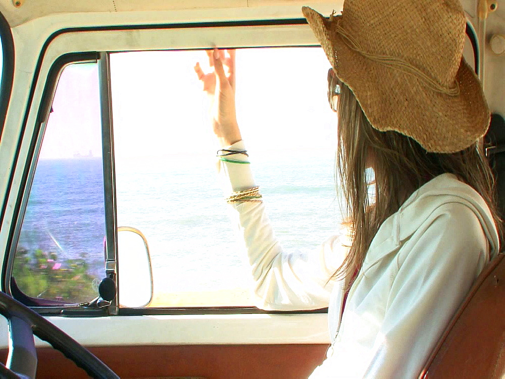 Brown haired woman driving a campervan