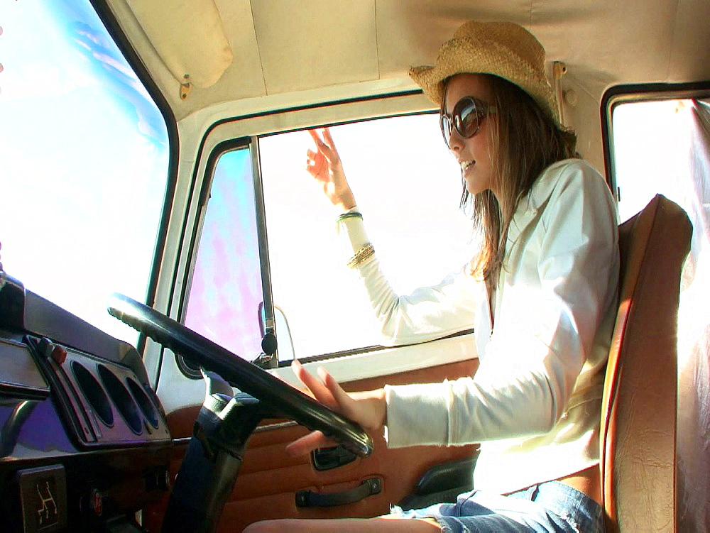 Woman with brown hair with her hands on the steering wheel of a campervan