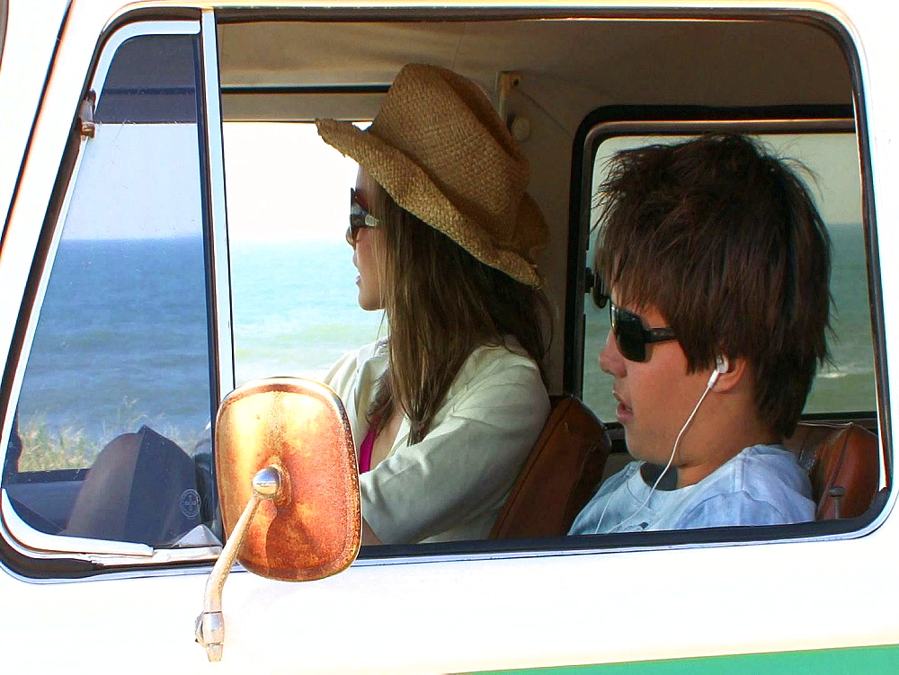 Young man and woman driving past the sea
