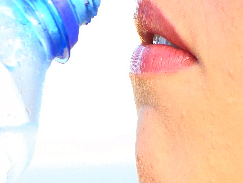 Woman with pink lipstick sipping water