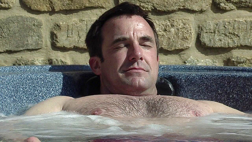 Brunette with a hairy chest lying in hot water